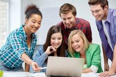 Groupe d'étudiants heureux de lycée avec l'ordinateur portable Images libres de droits