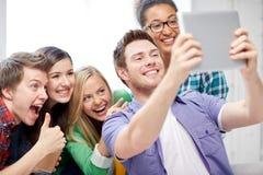 Groupe d'étudiants heureux de lycée avec le PC de comprimé Photos stock