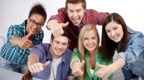 Groupe d'étudiants heureux montrant des pouces  Photographie stock libre de droits