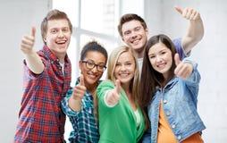 Groupe d'étudiants heureux montrant des pouces  Image libre de droits
