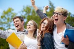 Groupe d'étudiants heureux montrant le geste de triomphe Photographie stock