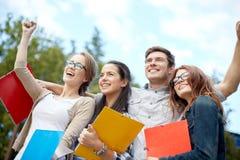 Groupe d'étudiants heureux montrant le geste de triomphe Photo stock