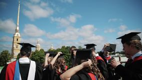 Groupe d'étudiants heureux recevant un diplôme la position en vent dehors dans la ville clips vidéos