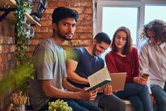Groupe d'étudiants interraciaux avec l'ordinateur portable et le livre faisant des leçons dans le dortoir d'étudiant images stock