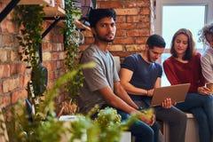 Groupe d'étudiants interraciaux avec l'ordinateur portable et le livre faisant des leçons dans le dortoir d'étudiant photo libre de droits