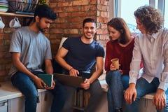 Groupe d'étudiants interraciaux avec l'ordinateur portable et le livre faisant des leçons dans le dortoir d'étudiant photos libres de droits