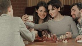 Groupe d'étudiants jouant des échecs, tout en prenant la photo de selfie Images libres de droits