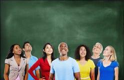 Groupe d'étudiants multi-ethniques recherchant avec le tableau noir photos stock