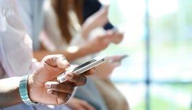 Groupe d'étudiants observant des smartphones Dépendance des jeunes aux tendances de nouvelle technologie Image libre de droits