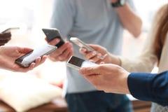Groupe d'étudiants observant des smartphones Dépendance des jeunes aux tendances de nouvelle technologie Photo libre de droits