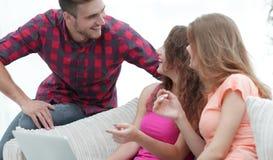 Groupe d'étudiants parlant, s'asseyant sur le divan Photos stock