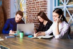 Groupe d'étudiants qualifiés apprenant ensemble dans la bibliothèque photos libres de droits