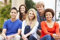 Groupe d'étudiants racial multi s'asseyant dehors Photo stock
