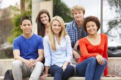 Groupe d'étudiants racial multi s'asseyant dehors Image libre de droits