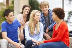 Groupe d'étudiants racial multi s'asseyant dehors Photos stock