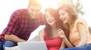 Groupe d'étudiants regardant un écran d'ordinateur portable, s'asseyant sur le couc Photo libre de droits