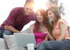 Groupe d'étudiants regardant un écran d'ordinateur portable, s'asseyant sur le couc Image libre de droits