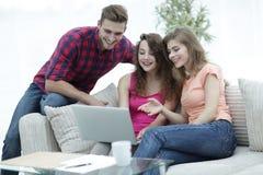 Groupe d'étudiants regardant un écran d'ordinateur portable, s'asseyant sur le divan Photographie stock libre de droits