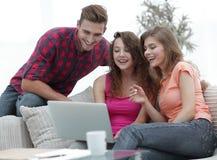 Groupe d'étudiants regardant un écran d'ordinateur portable, s'asseyant sur le divan Photo libre de droits