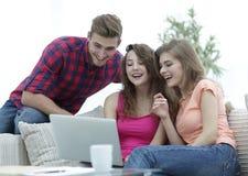 Groupe d'étudiants regardant un écran d'ordinateur portable, s'asseyant sur le divan Image stock