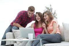 Groupe d'étudiants regardant un écran d'ordinateur portable, s'asseyant sur le divan Image libre de droits
