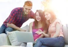 Groupe d'étudiants regardant un écran d'ordinateur portable, s'asseyant sur le divan Photographie stock