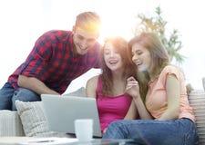 Groupe d'étudiants regardant un écran d'ordinateur portable, s'asseyant sur le divan Photos stock