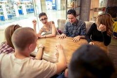 Groupe d'étudiants s'asseyant dans une barre de café regardant l'un l'autre Photos libres de droits