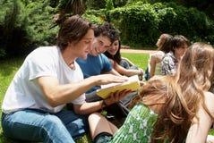 Groupe d'étudiants s'asseyant en stationnement Image libre de droits