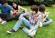 Groupe d'étudiants s'asseyant en stationnement Photographie stock