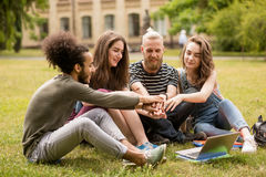 Groupe d'étudiants s'asseyant sur l'herbe dans le jardin d'université Photo stock