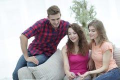 Groupe d'étudiants s'asseyant sur le sofa dans le salon Photo stock