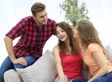 Groupe d'étudiants s'asseyant sur le sofa dans le salon Photo libre de droits