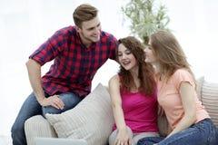 Groupe d'étudiants s'asseyant sur le sofa dans le salon Image stock