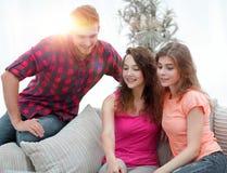 Groupe d'étudiants s'asseyant sur le sofa dans le salon Photographie stock