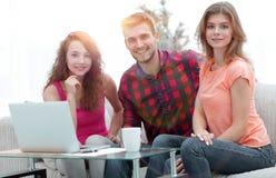 Groupe d'étudiants s'asseyant sur un divan derrière une table basse Image stock