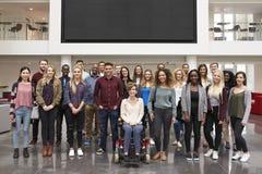 Groupe d'étudiants se tenant dans l'oreillette sous un grand écran de poids du commerce Photo libre de droits