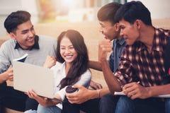 Groupe d'étudiants souriant comme ils utilisent l'ordinateur portable images libres de droits