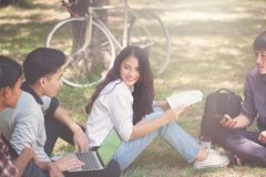 Groupe d'étudiants travaillant dehors ensemble dans le campus, images libres de droits