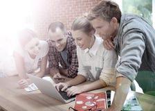 Groupe d'étudiants travaillants sur un ordinateur portable Images libres de droits
