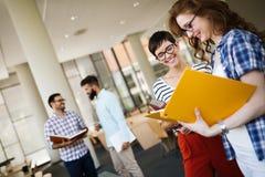 Groupe d'étudiants universitaires étudiant à la bibliothèque Photographie stock