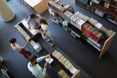 Groupe d'étudiants universitaires étudiant à la bibliothèque Photos stock