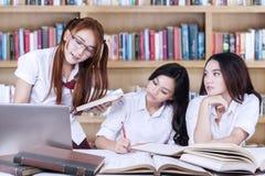 Groupe d'étudiants universitaires étudiant dans la bibliothèque Images stock