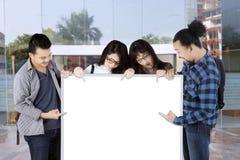 Groupe d'étudiants universitaires se dirigeant sur le conseil blanc avec l'espace de copie Images libres de droits