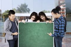 Groupe d'étudiants universitaires se dirigeant sur le conseil vert avec l'espace de copie Photos libres de droits
