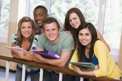 Groupe d'étudiants universitaires se penchant sur la rampe image libre de droits