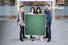 Groupe d'étudiants universitaires tenant un conseil vert avec l'espace de copie Image stock
