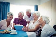 Groupe d'aînés à l'aide d'une tablette Images libres de droits