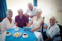 Groupe d'aînés à l'aide d'une tablette Image stock