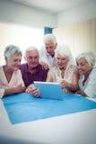 Groupe d'aînés à l'aide d'une tablette Photo stock